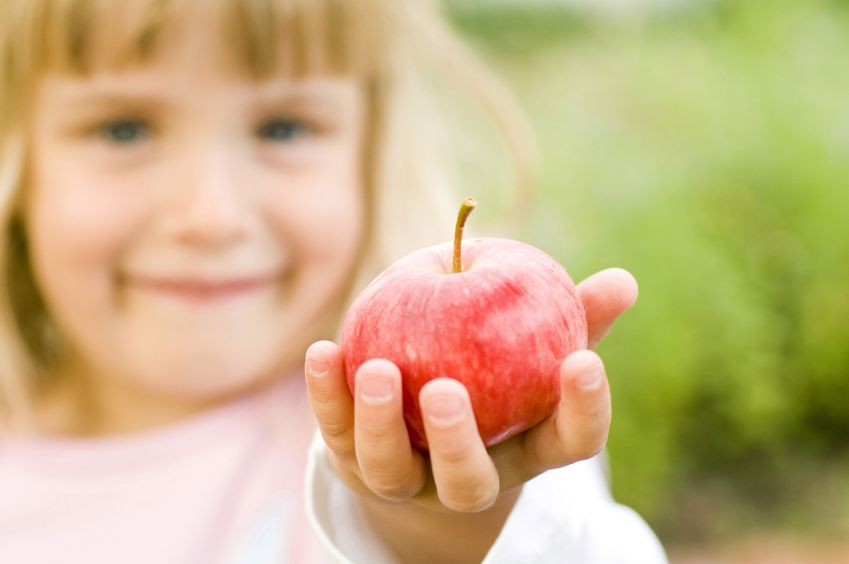 little girl holding apple