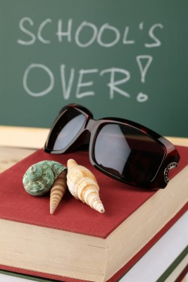 Schools out summer vacation seashells on textbook in front of chalkboard