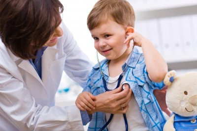 doctor listening to young boy's heart
