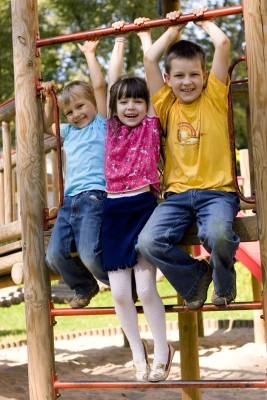 three kids playing on playground