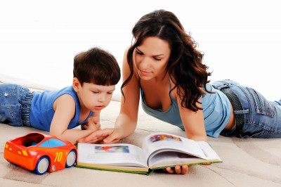 nanny with young boy reading a book