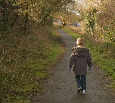 little boy walking alone in the woods