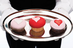 three cupcakes with heart shaped icing on a silver platter