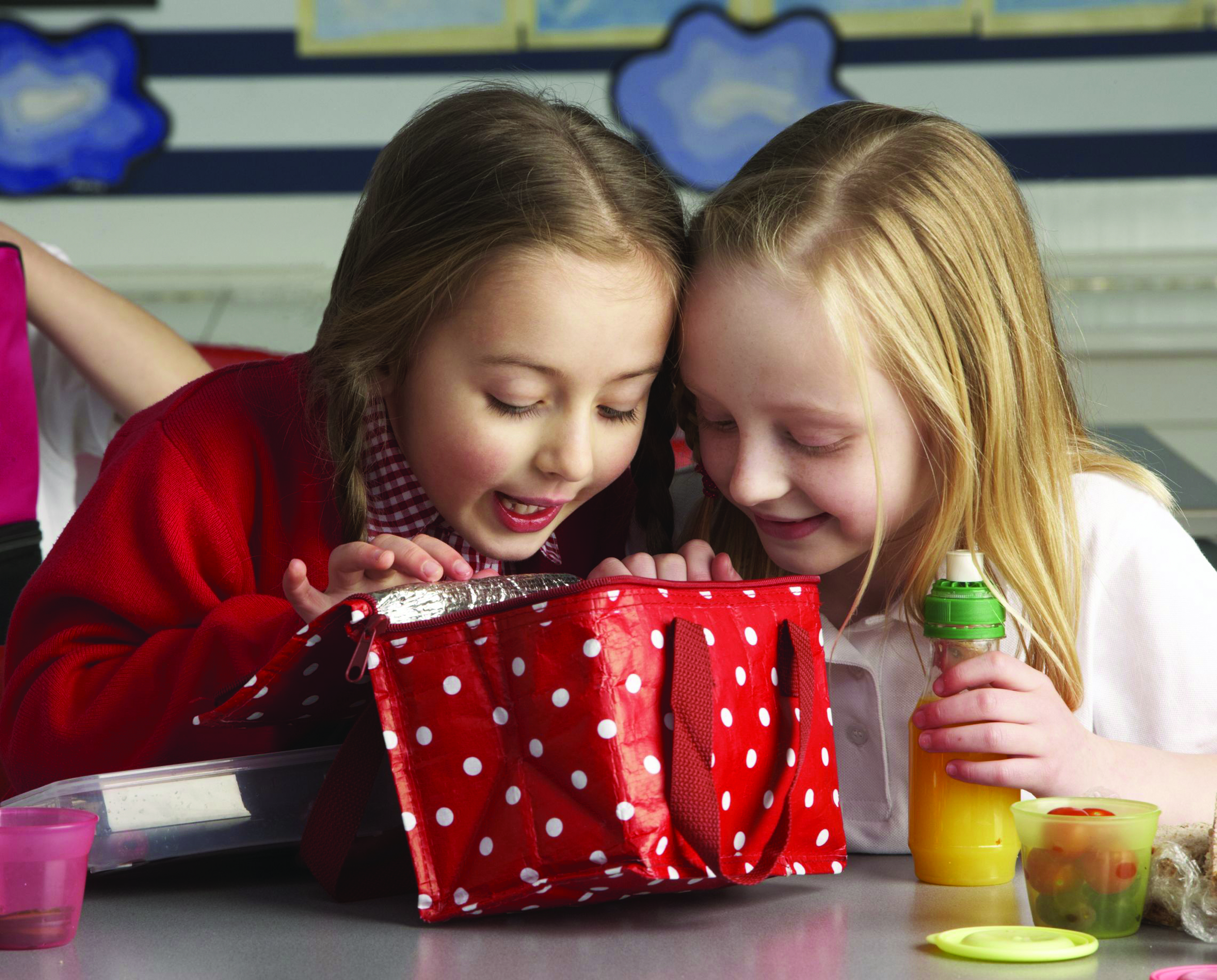 two young girls eating lunch at school