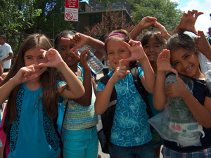 Children from Children's Aid Society doing the Super Power 'S' sign.