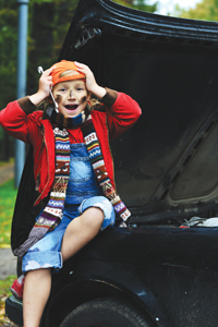 little girl in dirty clothes sitting on car holding mechanic tools
