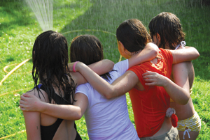 girls arm in arm around a sprinkler