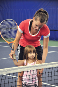 tennis instructor teaching little girl to play tennis