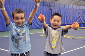 Two little boys on tennis court