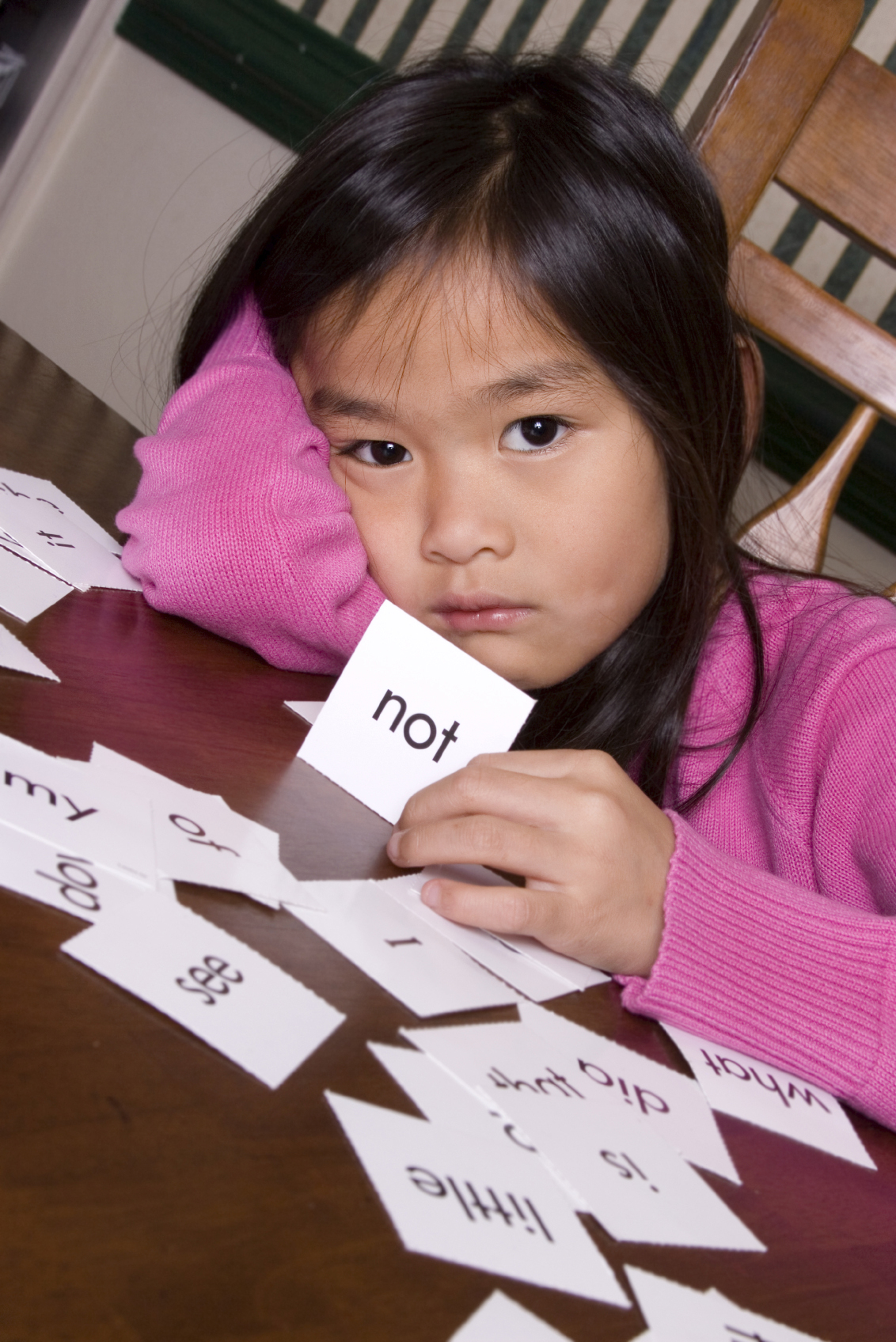 Sad young girl using flash cards learning vocabulary