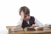 Young boy reading a books at a desk looking frustrated.
