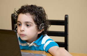 boy playing computer games, wearing headphones
