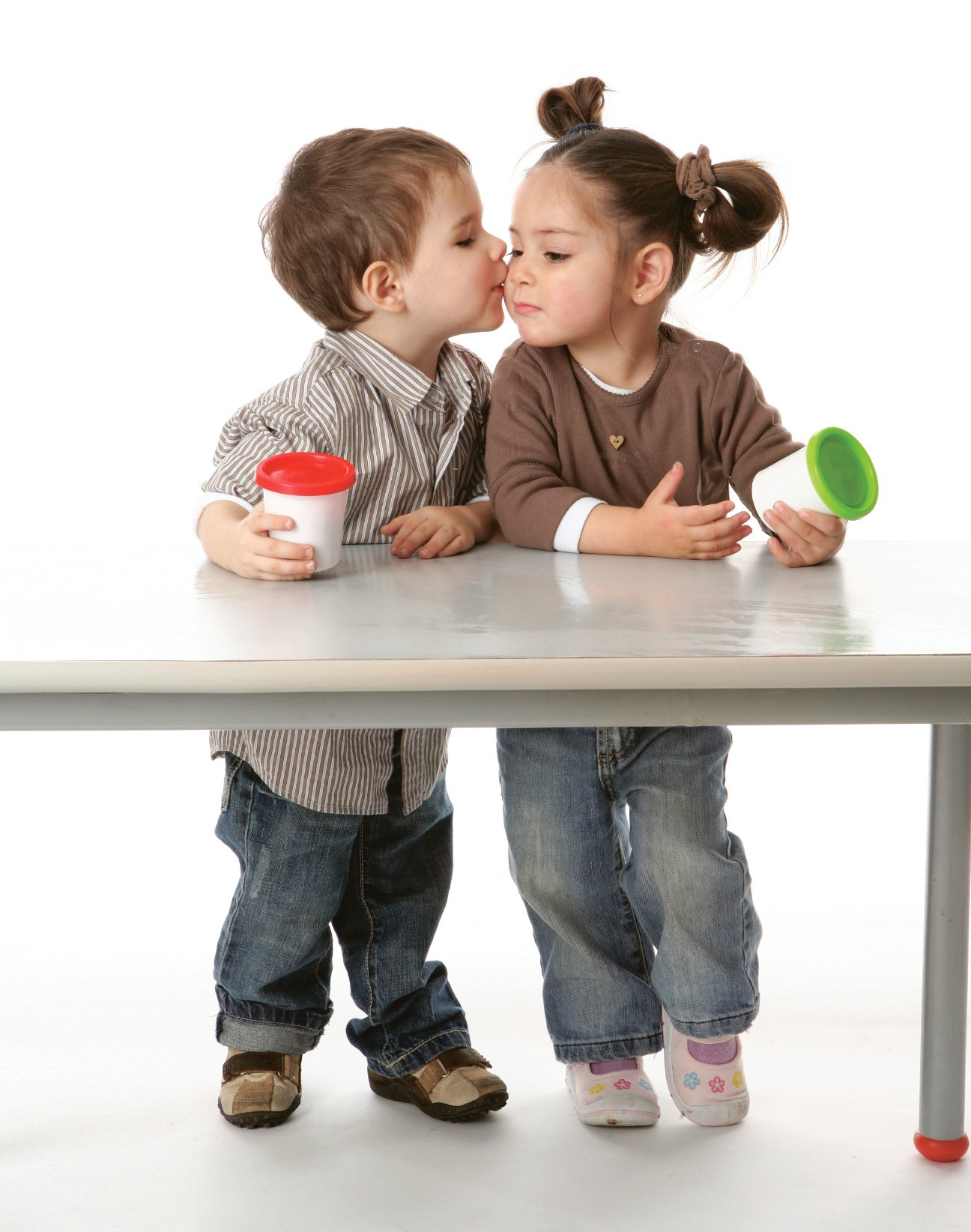 A young boy and girl kissing at a desk