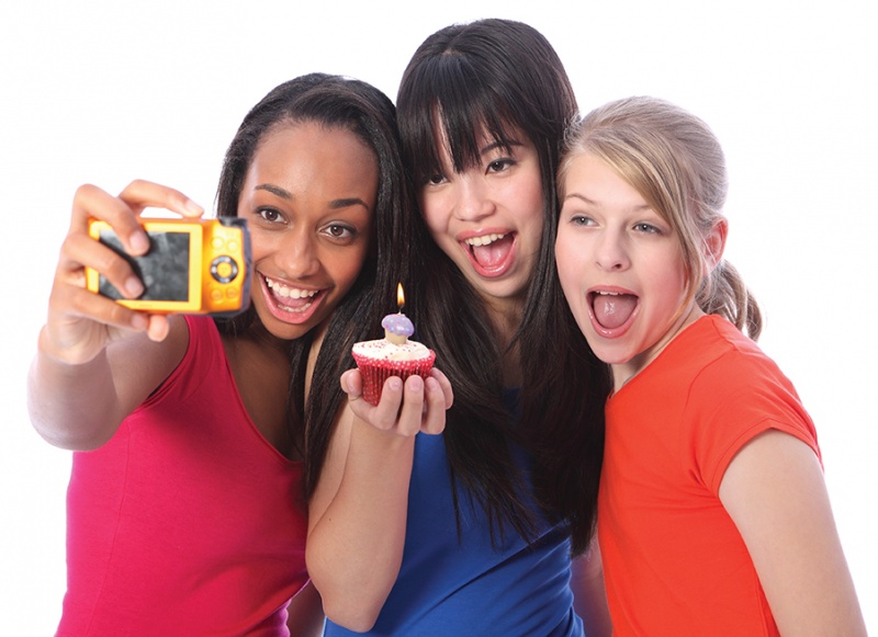 three tween girls taking selfie with cupcake