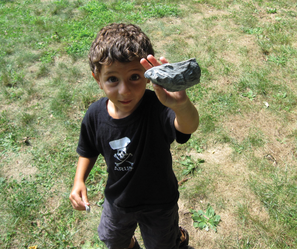 young boy holding a rock on earth day