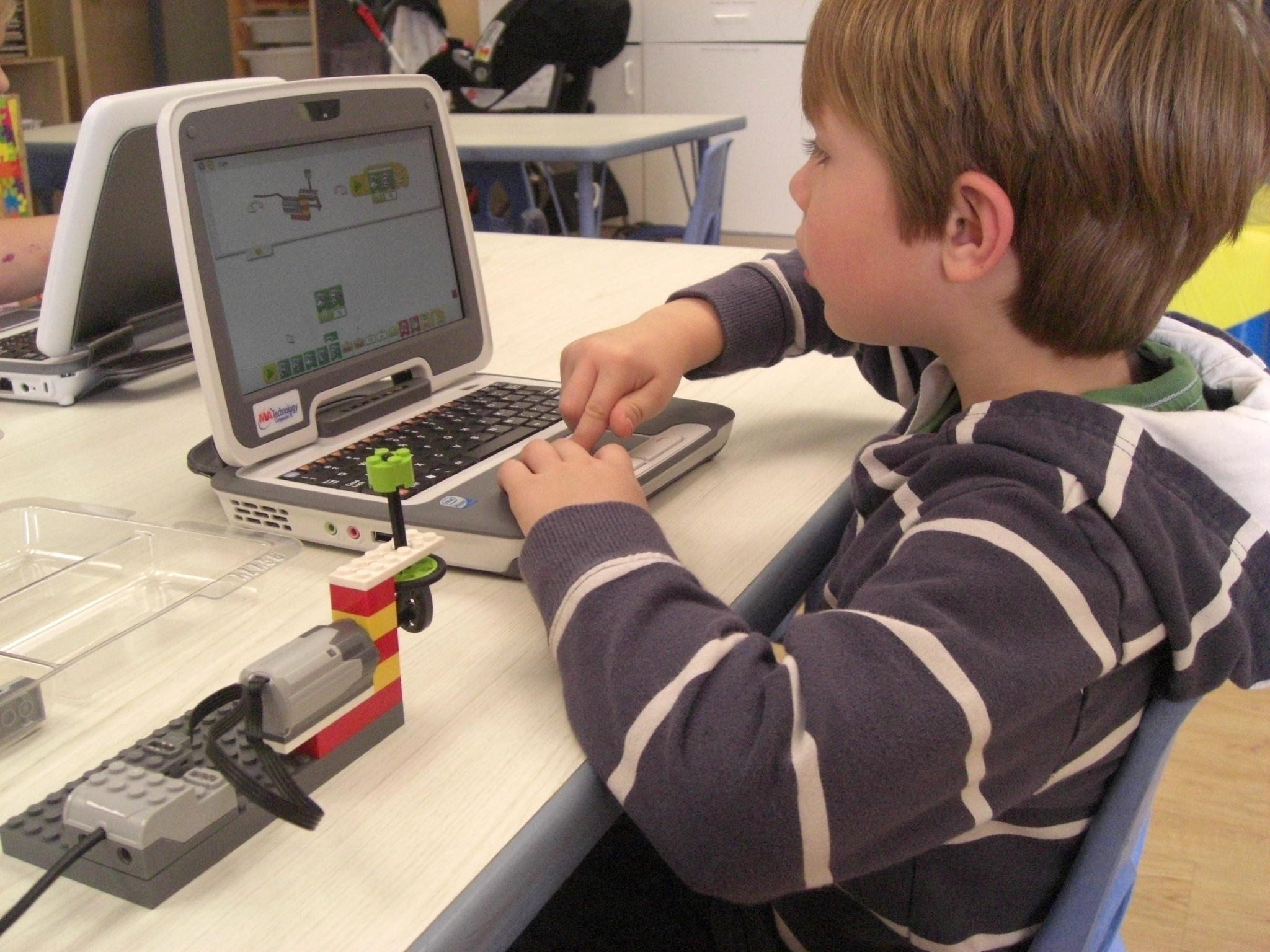 Max Crothall, 6, uses a computer to build and program a robot to move and make sound. Kids can do this at Bricks and Motors in Rye Brook, Westchester.