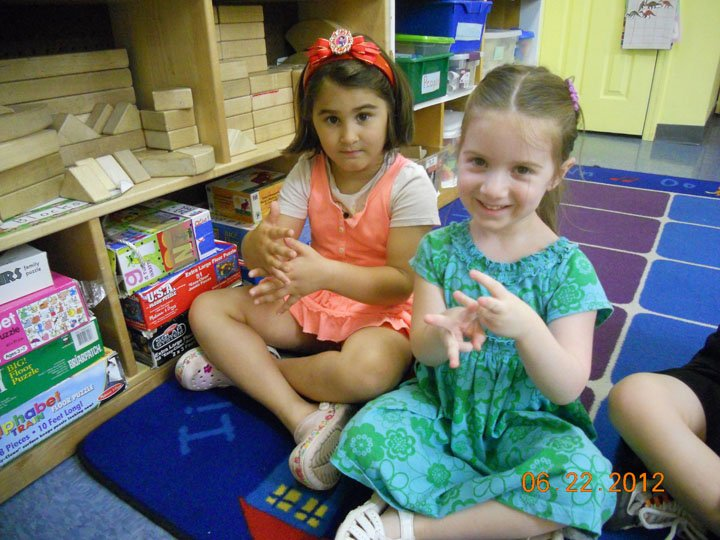 Two preschool girls at The Growing Tree Nursery School show their American Sign Language Skills.