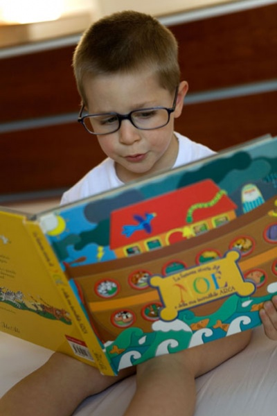 boy wearing glasses while reading a book