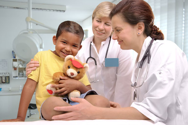 Two female doctors with boy holding a teddy bear