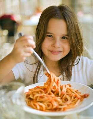 girl eating spaghetti in restaurant