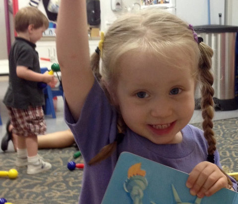 preschool girl raises her hand to answer a question