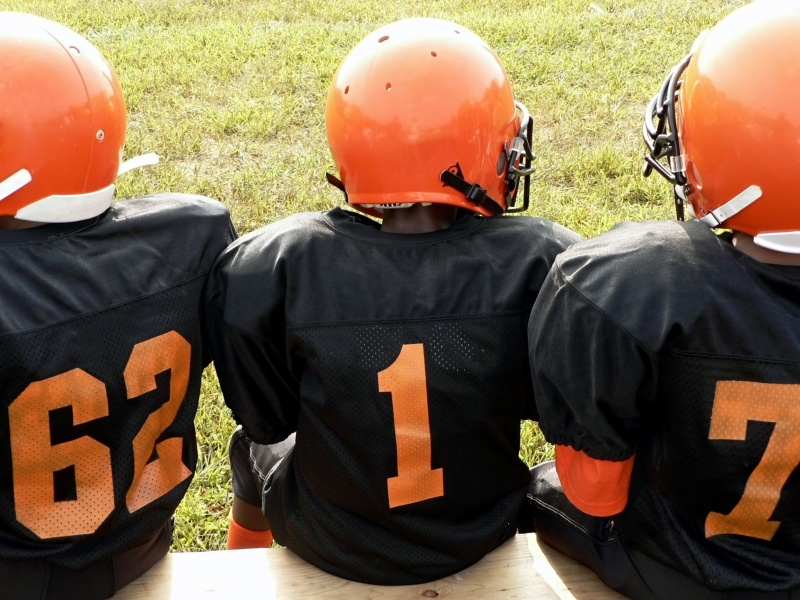 Young football players sitting on the sideline