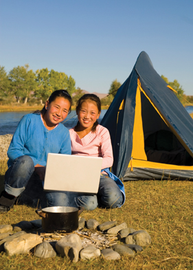 campers with laptop outside