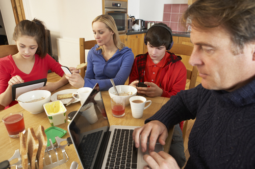 Family on their computers and cell phones at the dinner table