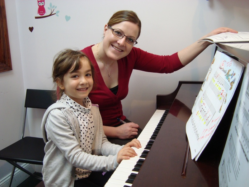 teacher and child sitting at piano