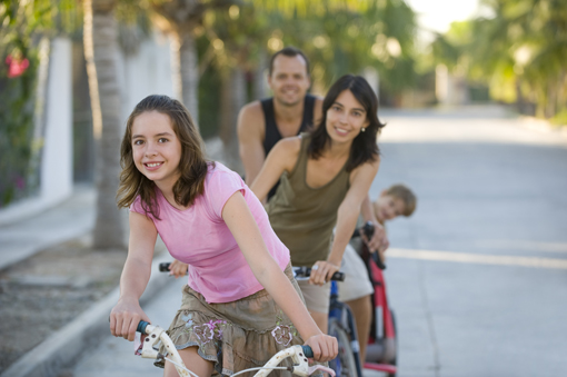 family riding bikes on street