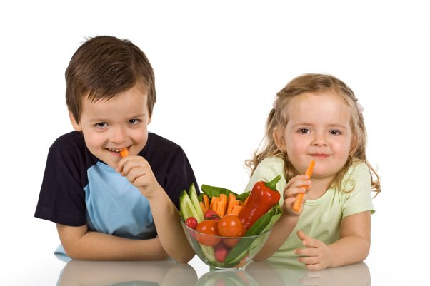 young boy and girl eating vegetables