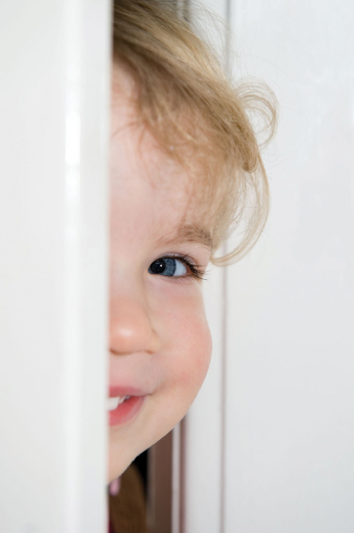 child peeking through door