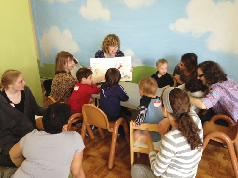 A teacher at GiGi's Playhouse teaching kids to read