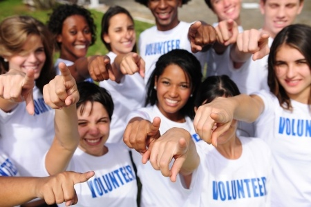 Group of Volunteers pointing towards the Camera