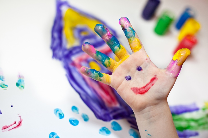 child's hand covered in finger paint