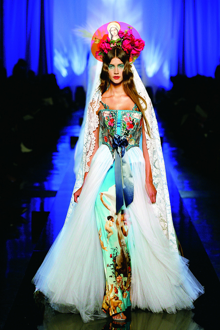 """Apparitions"" gown from Jean Paul Gaultier's ""Virgins (or Madonnas)"" women's haute couture spring-summer collection of 2007.""Celestial"" print satin strapless sheath; bustier-style top with ""hologram"" embroidery and bows; ivory silk tulle overskirt; ""hologram"" and ivory lace veil. © Patrice Stable/Jean Paul Gaultier"