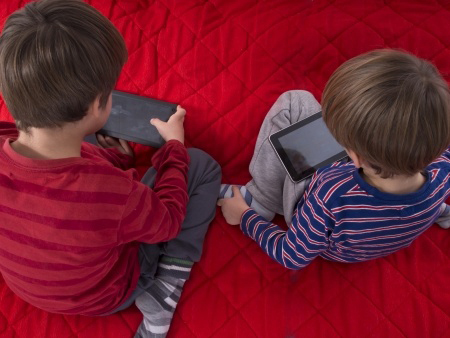 two young boys playing with tablets