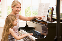 child playing piano with instructor