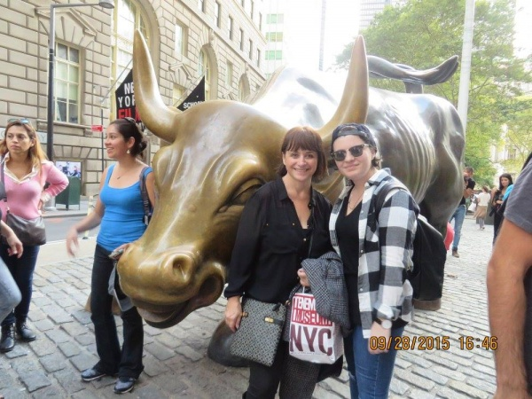tourists bull sculpture downtown