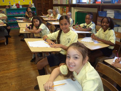 students writing at st joseph the worker catholic academy