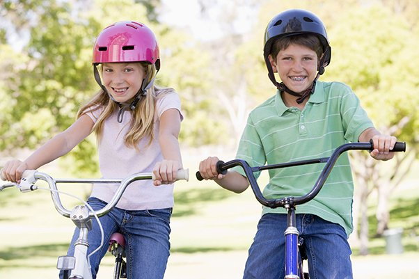 kids on bikes wearing helmets