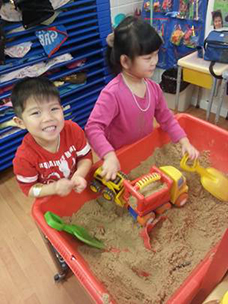 two children playing in appletree day care center's sandbox