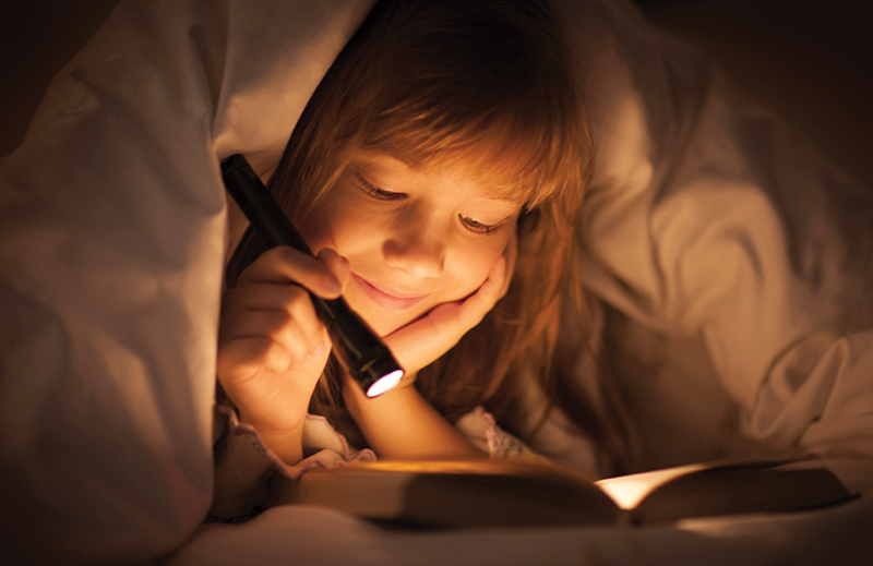 girl reading under covers with flashlight