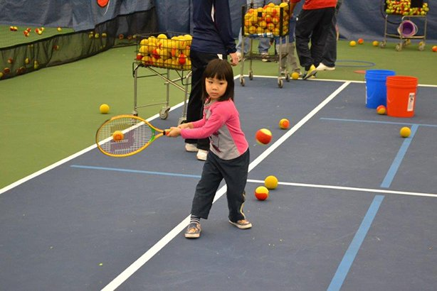 young girl playing tennis