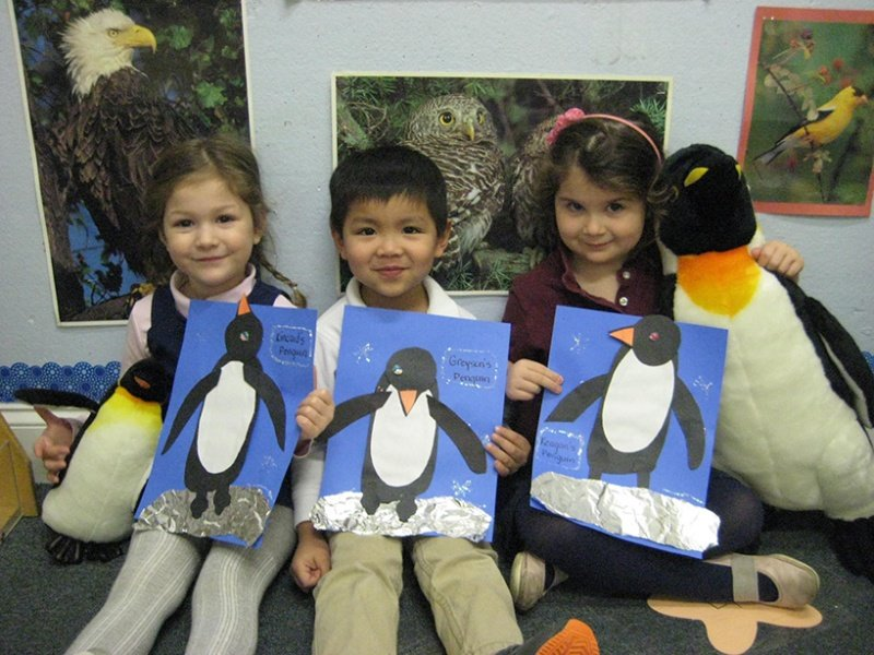 children holding construction paper penguins